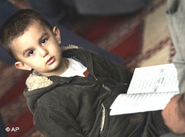 Muslim boy holding a Koran (photo: AP)