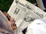 Arab woman reads newspaper, photo: AP