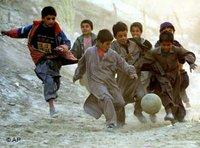 Afghan children play soccer in a dried-out riverbed in downtown Kabul (photo: AP)