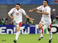 Tunisia's Santos, left, is congratulated by teammate Jawhar Mnari after scoring the opening goal during the Confederations Cup Group A soccer match between Australia and Tunisia in Leipzig, Germany June 2005 (photo: AP)