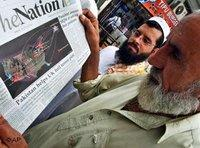 Two Pakistanis are reading the newspaper
