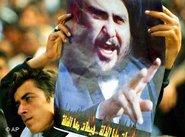 A man holding a poster displaying Shiite cleric al-Sadr (photo: AP)