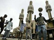 Nigerian youths playing soccer in front of a mosque (photo: AP)