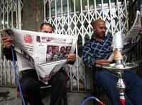Iraqi newspaper-readers in Baghdad (photo: AP)