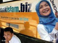 A passenger waits for bus in front of the Malaysian Islamic Bank billboard at a bus stop in Kuala Lumpur