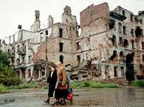 Local residents walk past destroyed buildings in Grozny, Chechnya (photo: AP)
