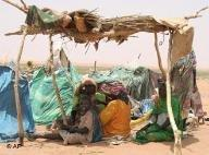 Darfur refugees, sitting under a make-shift shelter Sunday March 25, 2007, in this derelict section of Es Sallam camp say they have been waiting nine months to be relocated to decent shelters (photo: AP)