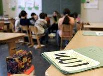 A file of teaching materials with the word Allah written in Arabic on the front lying on a table in a classroom (photo: dpa)