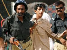 Pakistani police officers arrest a protester in Karachi, Pakistan, 14 May, 2007 (photo: AP)