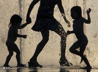 Silhouette of a woman with two children (photo: AP)