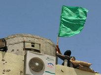 Hamas militant places a green Islamic flag on a guard tower of the Preventive Security headquarters in Gaza City (photo: AP)