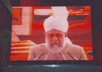 Hazrat Mirza Masroor Ahmad on an oversize video screen (photo: Andreas Gorzewski)