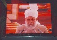 Hazrat Mirza Masroor Ahmad on an oversize video screen (photo: Andreas Gorzewski)