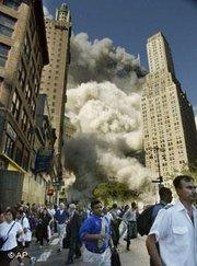 Pedestrians on Park Row flee the area of the World Trade Center as the center's south tower collapses following the terrorist attack on the New York landmark, 11 September 2001 (photo: AP)