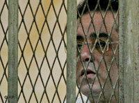 Ayman Nour, seen through the bars of the defendant's dock (photo: AP)