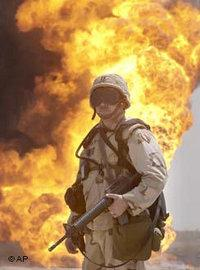 An unidentified US soldier stands guard as oil workers put out an oil well fire at Rumailah oil field, southern Iraq, April 2003 (photo: AP)