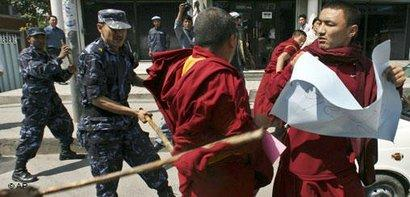 Policemen chase away protesters as Tibetans demonstrate against Chinese rule in Tibet (photo: AP)