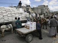 People waiting for supplies to be unloaded from a truck (Photo: AP)