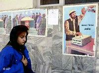 An Afghan woman passes by a poster encouraging to take part in the poll on the new constitution (photo: AP)