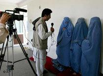 Afghan unidentified women clad in burqas are interviewed by a TV crew member (photo: AP)