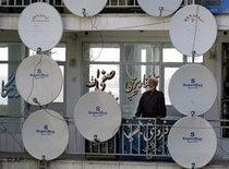 An Afghan man stands amongst several TV satellite dishes (photo: AP)