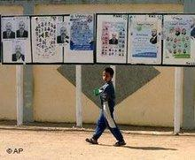 Boy in front of election posters (photo: AP)