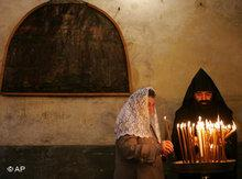 An Armenian Orthodox priest and a worshipper light candles following the Armenian Christmas Eve procession in the Church of the Nativity, traditionally believed to be the birthplace of Jesus Christ, in the West Bank town of Bethlehem, 18 January 2007 (photo: AP)