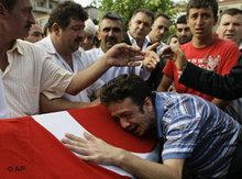 An unidentified Turkish man mourns over the flag draped coffin of an explosion victim during a funeral ceremony in Istanbul (photo: AP)