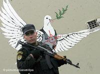 Palestinian security agent in front of a graffiti of a peace dove (photo: dpa)