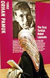 Woman with scarf in front of a poster of Orhan Pamuk at the Frankfurt Book Fair (photo: AP)