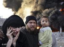 A Palestinian family rushes past a burning building after an Israeli missile strike in the Rafah refugee camp, southern Gaza Strip, Sunday, 28 December 2008 (photo: AP)