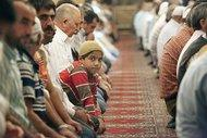 Young boy in the middle of a row of praying men in a mosque (photo: dpa)