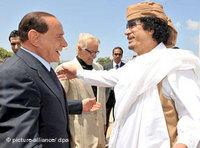 Silvio Berlusconi greets Muammar al-Gaddafi (photo: dpa)
