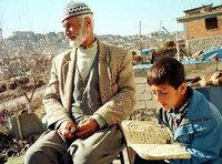 Ahmet Kaya, a 76-year-old Turkish Kurd, enjoys the sun as his grandson Feyyaz Kaya, 8, recites the Muslim's holy book or Koran in the ghetto outside of Diyarbakir