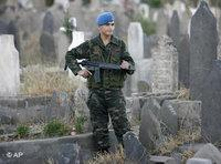 Turkish soldier on guard omn a graveyard (photo: AP)
