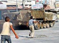 Palestinian children throw stones at an Israeli tank in the West Bank town of Jenin (photo: AP)