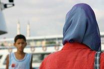Woman wearing the Muslim headscarf, a boy in the background (photo: Sirvan Sarikaya)