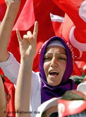 Turkish woman wearing headscarf at a protest rally; background: the Turkish natio al flag (photo: dpa)