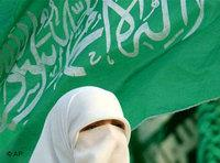 A veiled Palestinian woman stands in front of a Hamas flag as she attends a Hamas pre-election in 2006 (photo: AP)