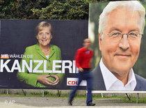 Frank-Walter Steinmeier and Angela Merkel on election posters (photo: AP)