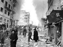 Civilians walk through the debris-laden Ben Yehuda street in Jerusalem following the explosion in the heart of the city's Jewish business district on Feb. 22, 1948 (photo: AP)