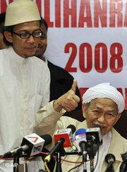 Nik Aziz, chief minister of Kelantan, right, during a press conference (photo: AP)