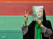 An Iranian protests, holding up a Mir Hossein Mousavi life-size photograph before his face, giving the victory sign (photo: AP)