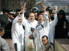 Some of 29 members of the banned Muslim Brotherhood clutch Qurans as they are led into a court in the New Cairo area of Cairo, Egypt Wednesday, Feb. 28, 2007. The court upheld Egypt's prosecution decision to freeze the assets of 29 members of the Muslim Brotherhood for financing a banned organization - causing a heavy loss for the country's most powerful opposition movement, which won 88 of parliament's 454 seats in 2005 elections with its candidates running as independents (photo: AP)