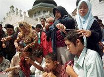 Acehnese women cut hair of four women suspected as prostitutes in front of Baiturrahman Mosque in the provincial capital of Banda Aceh, Aceh, Indonesia Sunday, 5 December 1999. Islamic law now is implemented by Muslim-affiliated separatists in the violence-wrecked region as they step up their campaign to break away from Indonesia (photo: AP)