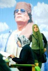 Female students in Libya in front of a poster of Col Gaddafi (photo: AP)