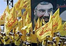 Hezbollah rally with activists holding a larger-than-life Nasrallah poster (photo: AP)