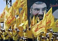 Hezbollah rally with activists holding a larger-than-life Nasrallah poster (photo: AP)