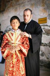 A boy with a candle and a priest during the ceremony (photo: Iason Athanasiadis)