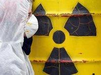 Man in protective clothing in front of a barrel of radioactive material (photo: dpa)